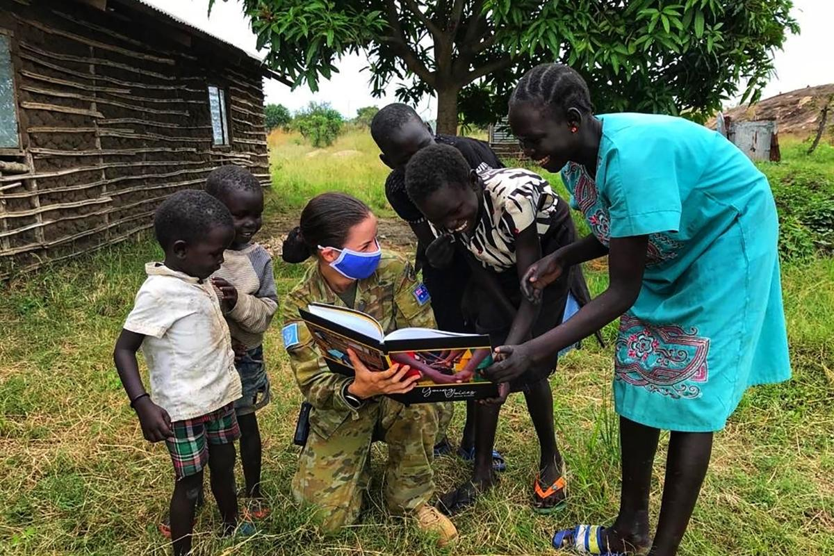 Captain Stephanie Palfrey–Sneddon shows school children in South Sudan her book Young Voices of South Sudan.
