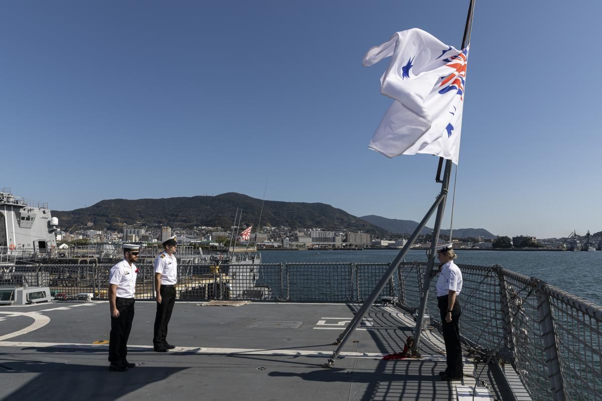 Members of HMAS Arunta's ship's company stand at attention during a Remembrance Day ceremony while alongside Sasebo Naval Base, Japan. Photo: Leading Seaman Jarrod Mulvihill