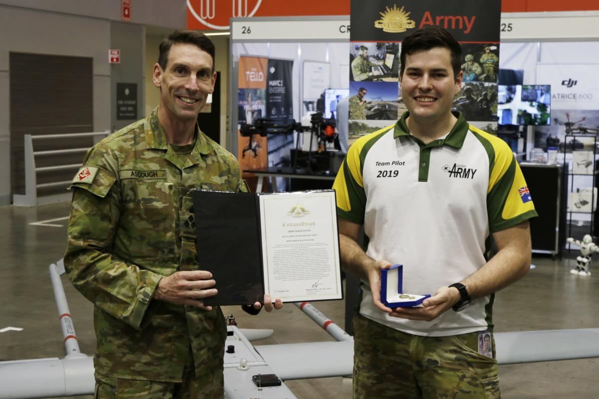 Commander 6 Brigade Brigadier Michael Ascough, left, presents Private Mackenzie Togo with an Army gold commendation.
