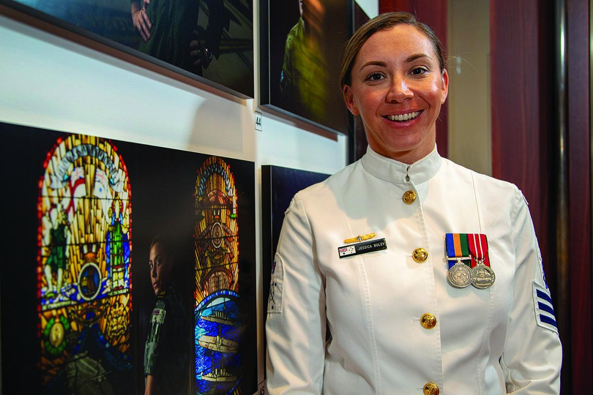 Then Petty Officer Jessica Buley stands beside her portrait in the 'thank you for your service' photographic exhibition in the Anzac Memorial, Hyde Park, Sydney last year. Photo: Chief Petty Officer Cameron Martin