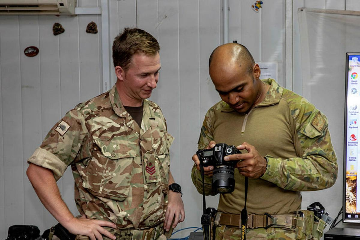 Australian soldier Corporal Nunu Campos, right, deployed with Task Group Taji 9, examines photographs taken by British soldier, Colour Sergeant Chorlton, during a photography workshop at the Taji Military Complex, Iraq. Photo: Corporal Tamara Cummings