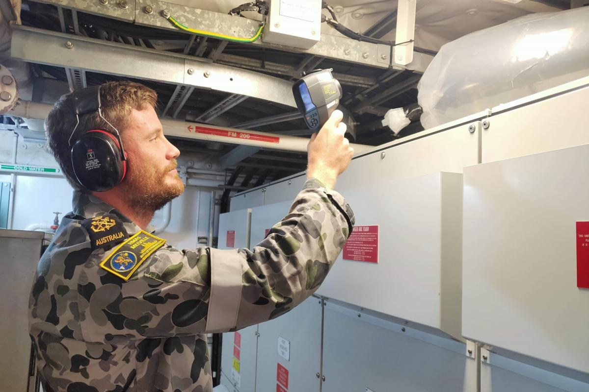 Petty Officer Ryan Schweitzer takes a temperature reading during the prototyping phase of the ventilation system enhancement.