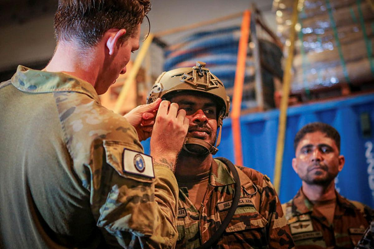 Australian Army soldier Lance Corporal Ethan Smith, left, fits a Bump Helmet to a member of the Sri Lankan Army aboard HMAS Canberra.