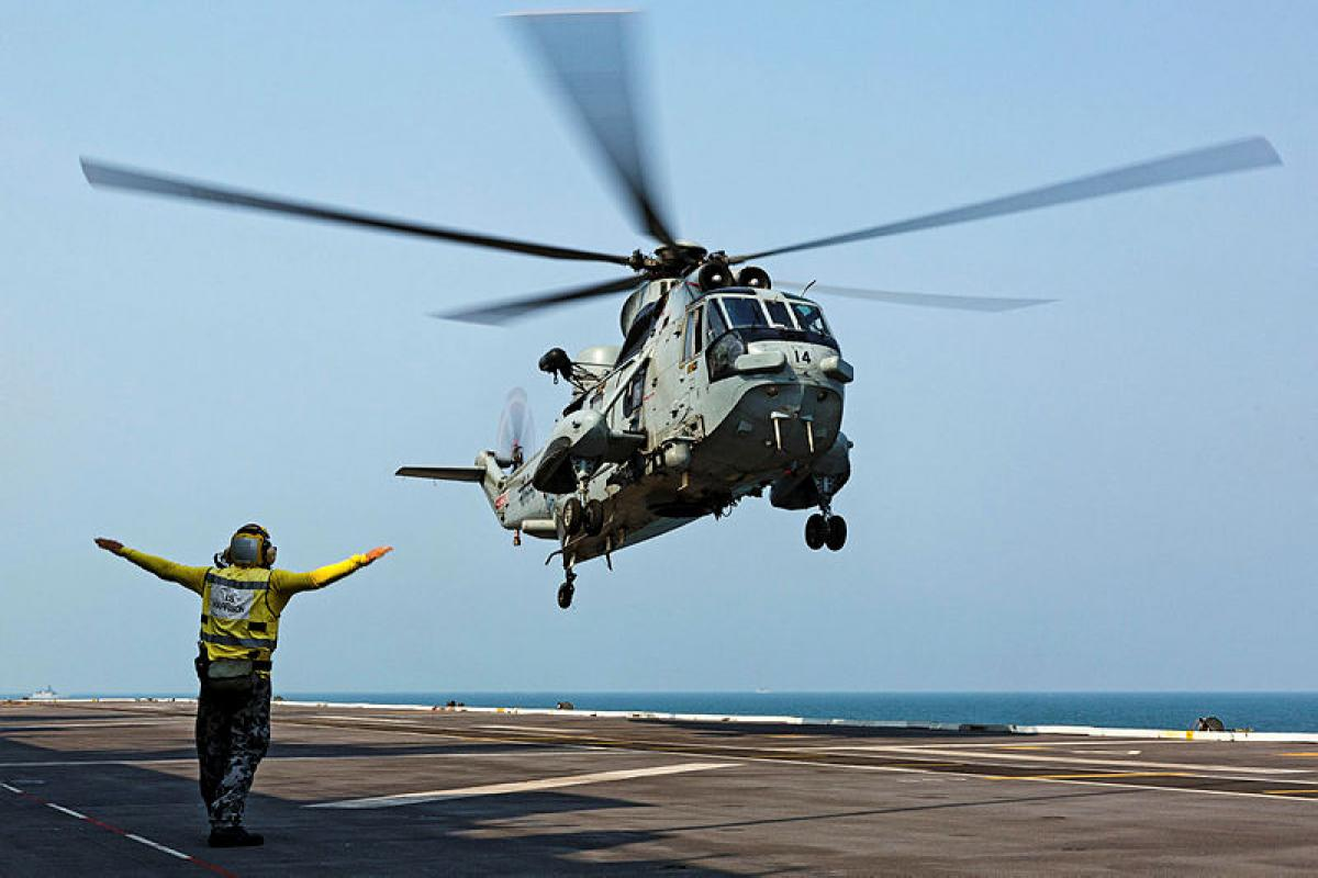 An Indian Navy Sea King helicopter lands on HMAS Canberra during cross-deck training exercises during AUSINDEX 2019.