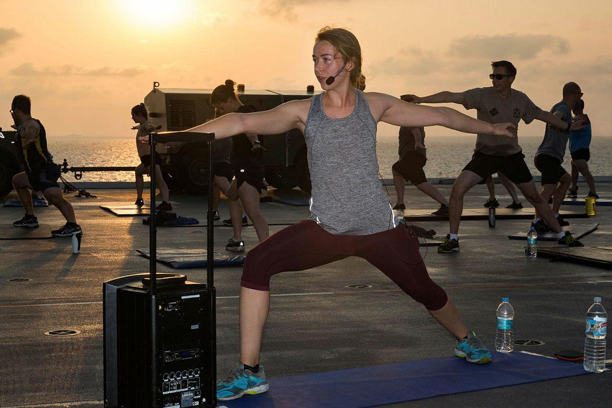 Lieutenant Nicola Hribar leads a sunrise yoga class for members of ship's company and embarked forces on the flight deck of HMAS Canberra during AUSINDEX 2019. Photo: Leading Seaman Steven Thomson