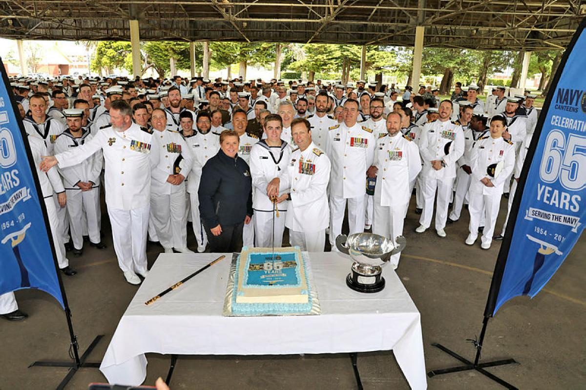 Chief of Navy, Vice Admiral Michael Noonan, and the youngest member of HMAS Cerberus, Seaman Trainee William Judd, together with Navy Canteens Manager Rhonda Gregg, cut the Navy Canteen's 65th birthday cake. Photo: Petty Officer Nina Fogliani
