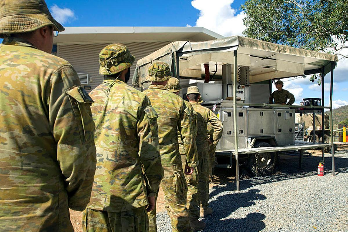 Soldiers line up as 1st Catering Company, 10th Forces Support Battalion, serves lunch from the Mobile Kitchen Trailer being trialed on Exercise Talisman Sabre 2019 in the Shoalwater Bay Training Area, Queensland. Photo: Corporal Tristan Kennedy