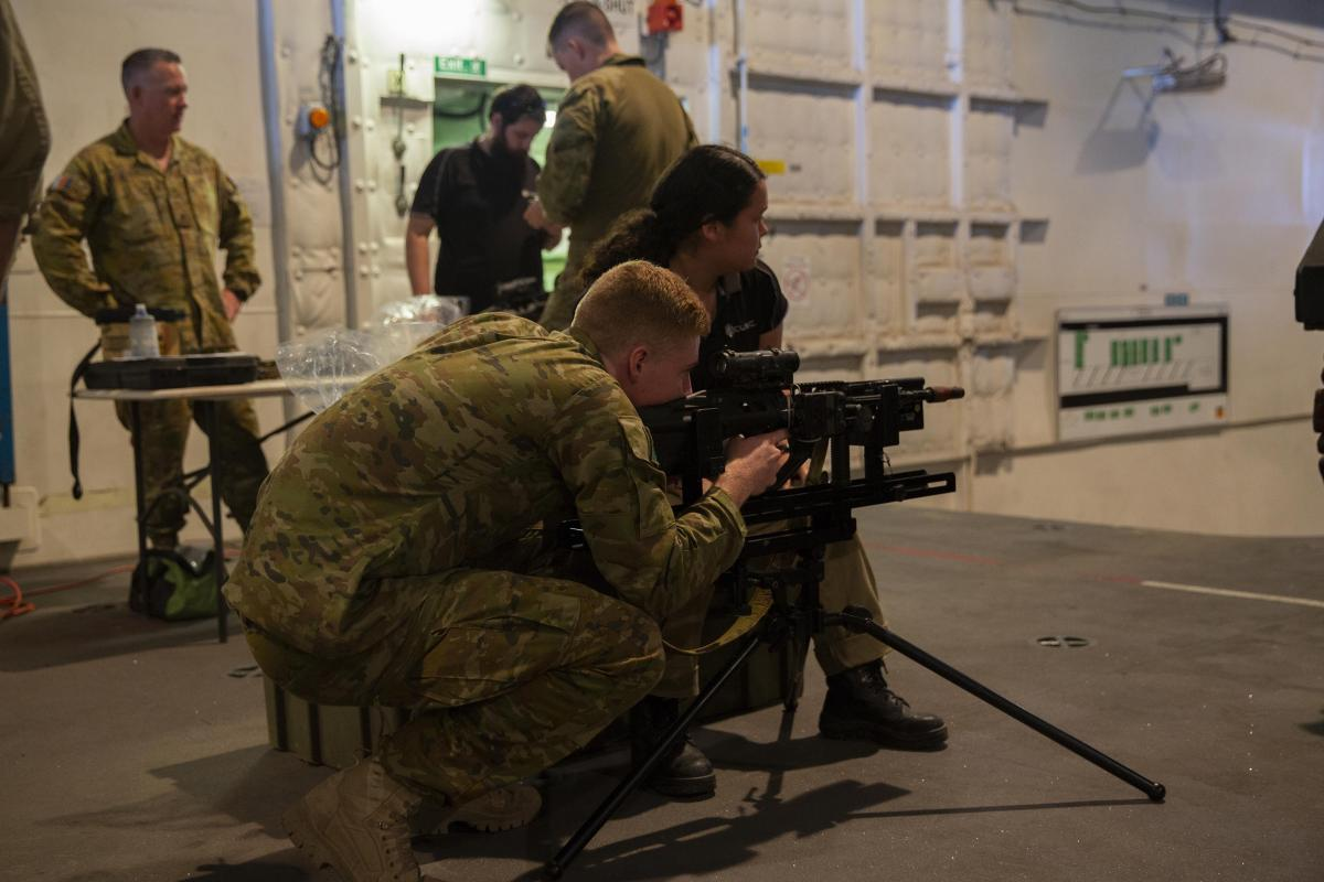 Cubic Defence Australia employee Celine Wood assists 7th Battalion, Royal Australian Regiment members in calibrating their weapons on HMAS Adelaide during Exercise Talisman Sabre 2019.