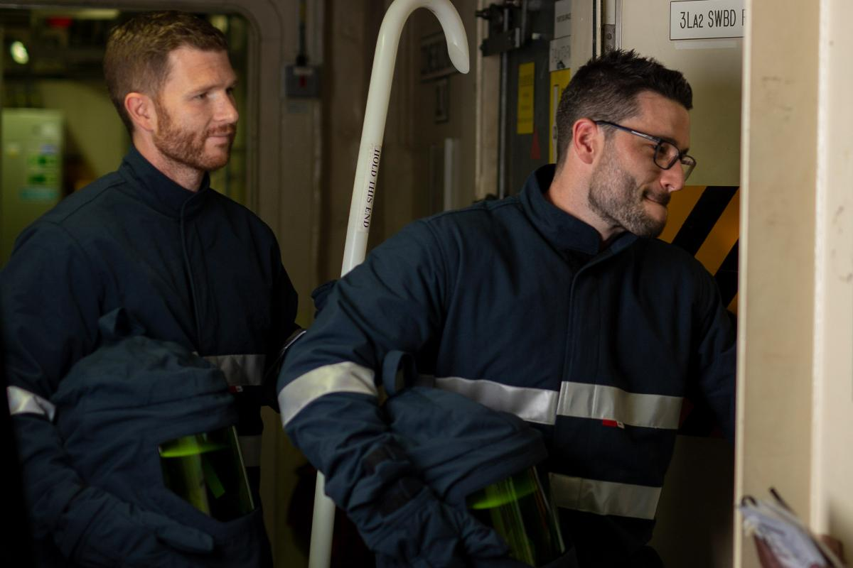 Leading Seamen Grant Cooney, left, and Joshua Finnigan prepare to enter the high-voltage switchboard room on board HMAS Choules.  Photo: Able Seaman Thomas Sawtell