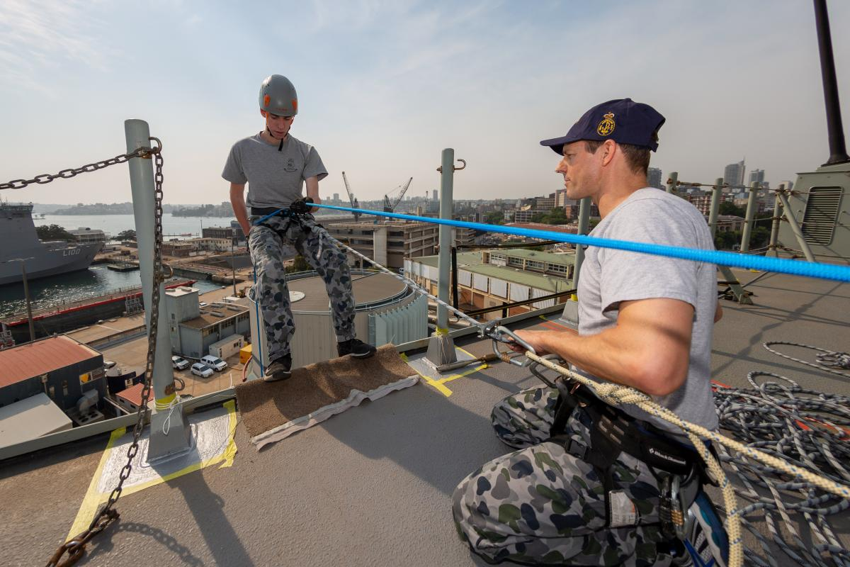 Petty Officer Shane Murphy  belays Seaman Riccardo De Florian from the upper decks of HMAS Canberra during the charity abseiling event. Photo: Able Seaman Jarrod Mulvihill