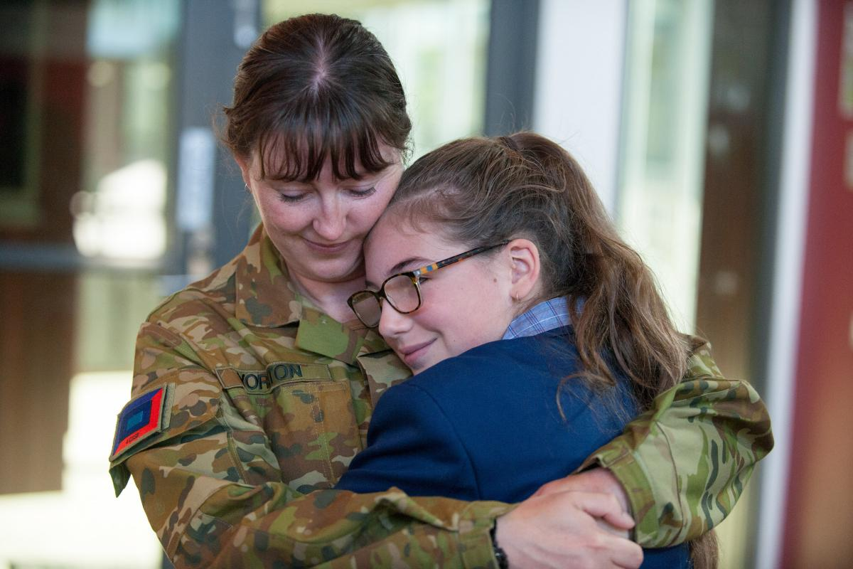 Corporal Marie Yorston and her niece, Allee, hug after their surprise reunion on her first day of high school. Photo: Private Michael Currie