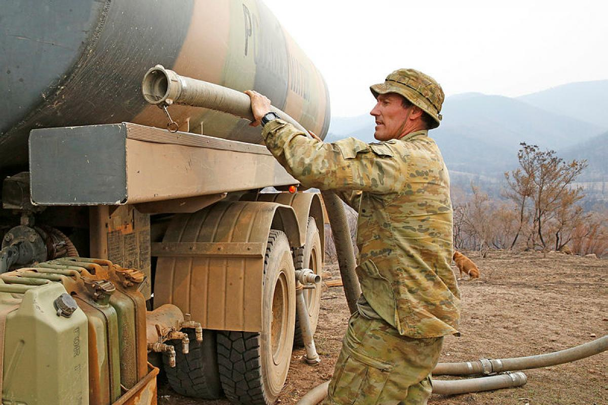 Army soldier Private Daniel Muntz assists property owners at a remote location on the New South Wales south coast with a resupply of 9000 litres of water. Photo: Sergeant Dave Morley