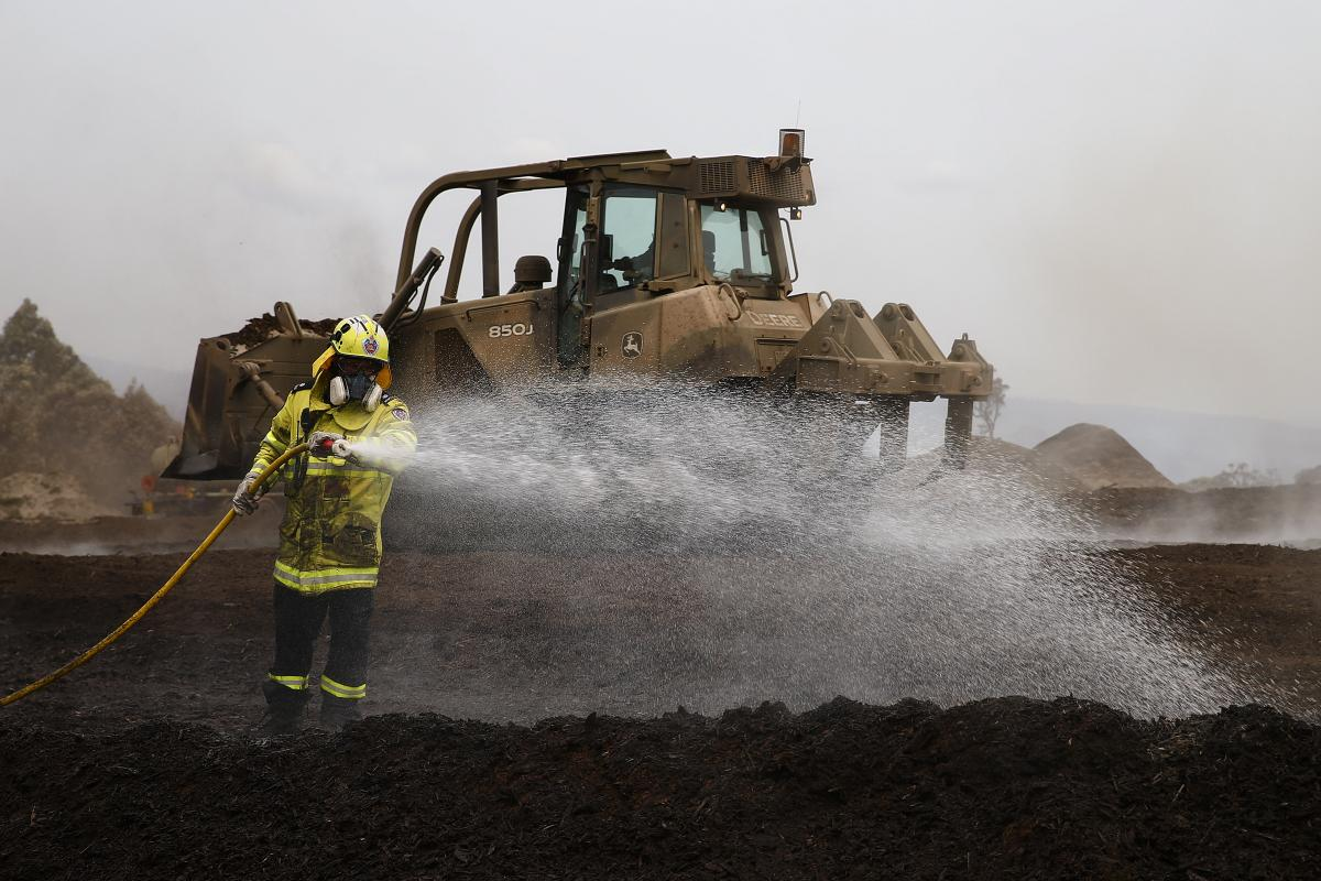 A NSW fireman works alongside an Army bulldozer to extinguish piles of mulch at Eden woodchip mill. Photo: Sergeant Max Bree