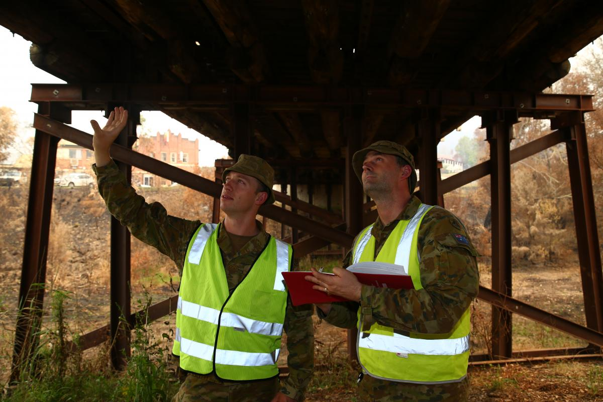 Army sappers Lance Corporal Rick Williams, left, and Corporal Ross Lorenz, of the 5th Engineer Regiment, inspect a fire-damaged bridge in Cobargo. Photo: Sergeant Max Bree
