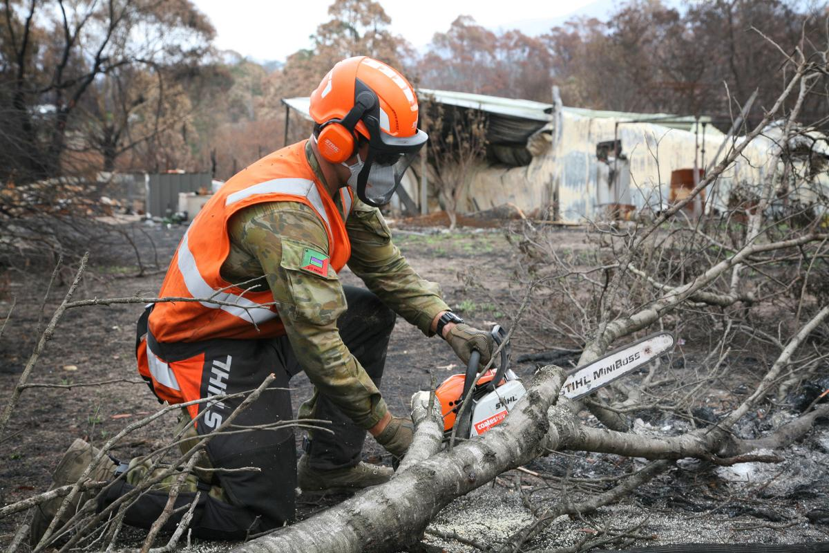 An Army Reserve infantryman from the 2/17th Battalion, Royal NSW Regiment, Private Jake Jubelin, clears a track to a destroyed property near Bega. Photo: Major Cameron Jamieson