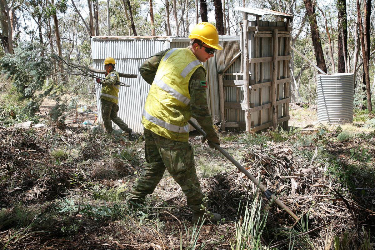 Private Ben Keogh uses a fire rake to clear vegetation away from the historic Bendora hut, located high in the Namadgi National Park in the ACT. Photo: Major Cameron Jamieson