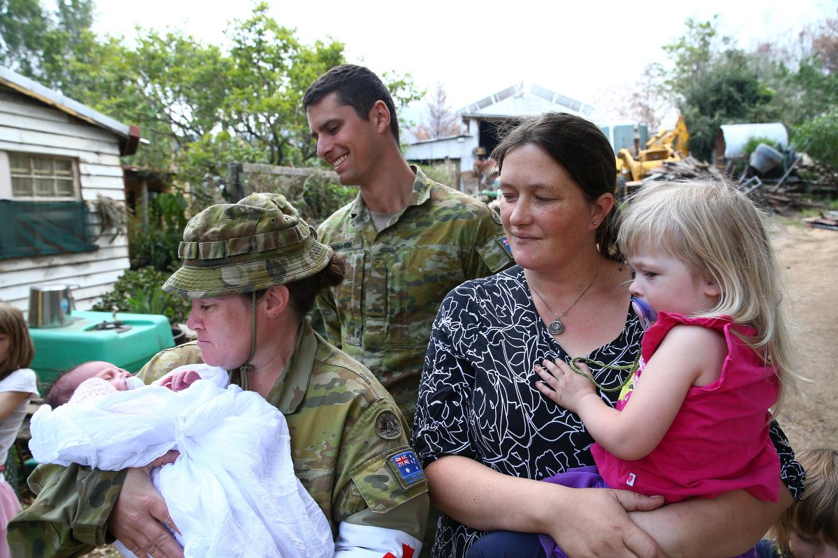 Corporal Kristie Connell, of the 8th Combat Service Support Battalion, and Private Nicholas Brimmer, of the 2nd/17th Battalion, Royal New South Wales Regiment, with Sarah and Ruby Tyrrell and baby Ivy. Photo: Sergeant Max Bree