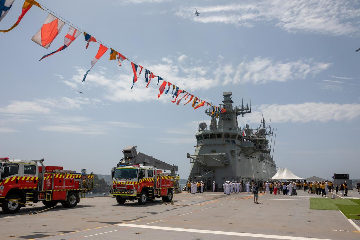 HMAS Canberra provides a perfect platform for NSW Rural Fire Service personnel and other guests as F/A-18 Hornets from the Royal Australian Air Force fly over Sydney Harbour during Australia Day celebrations. Photo: Leading Seaman Christopher Szumlanski