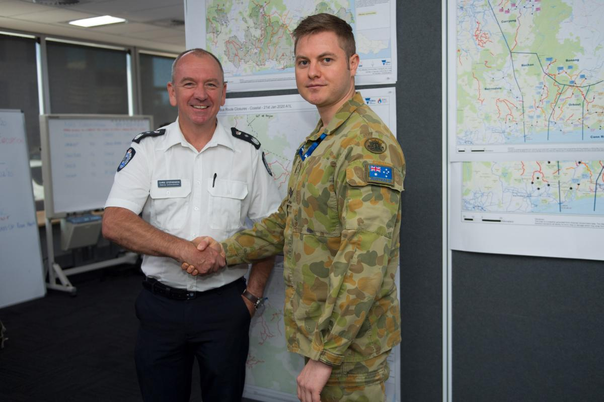 Chris Stephenson, Deputy Commissioner Emergency Management Victoria, thanks Sergeant Ryan Hodgson on his last day at the SCC. Photo: Private Michael Currie