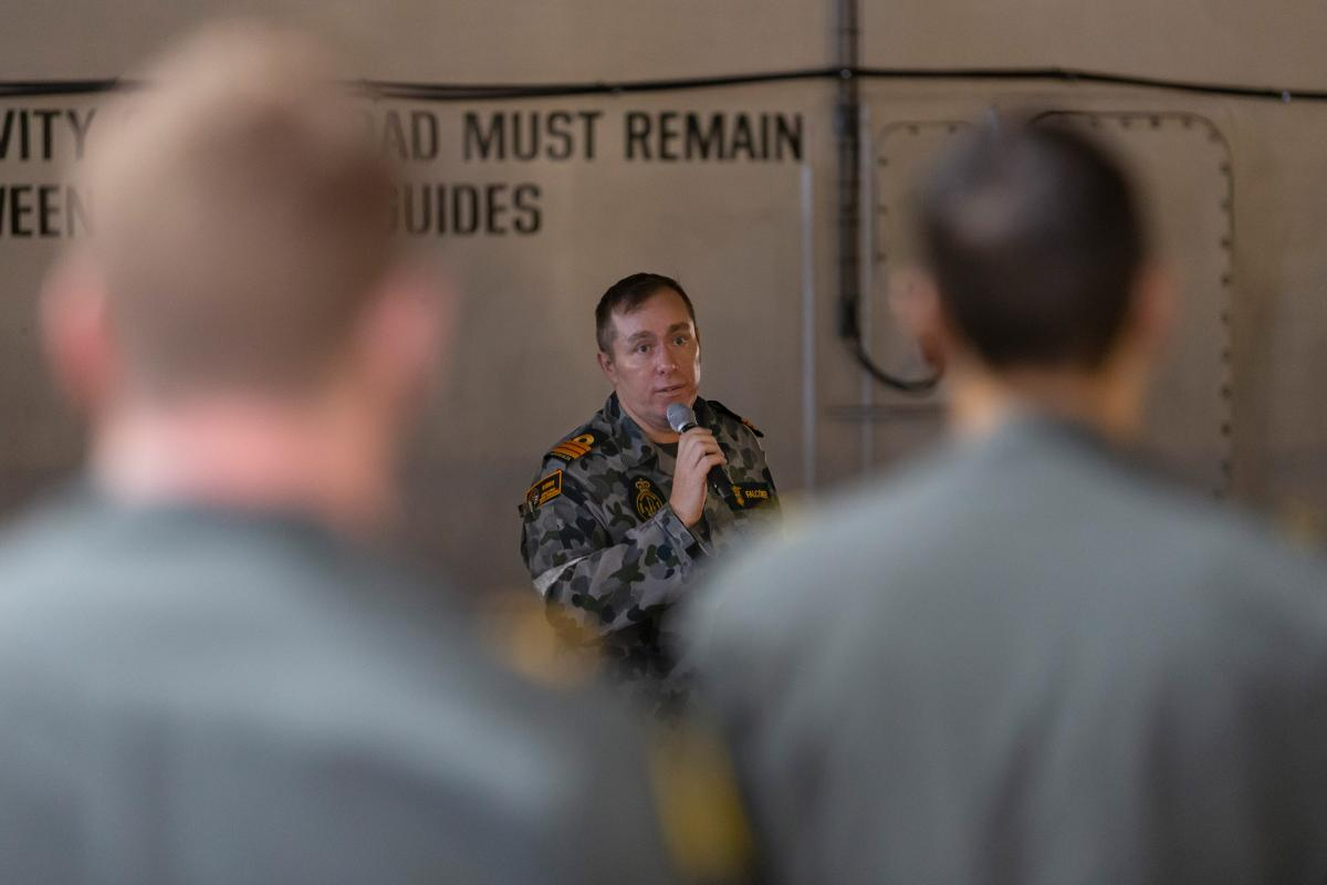 Commander Douglas Falconer briefs aviation personnel on board HMAS Adelaide before the ship begins first-of-class flight trials off the coast of Queensland earlier this month. Photo: Able Seaman Jarrod Mulvihill