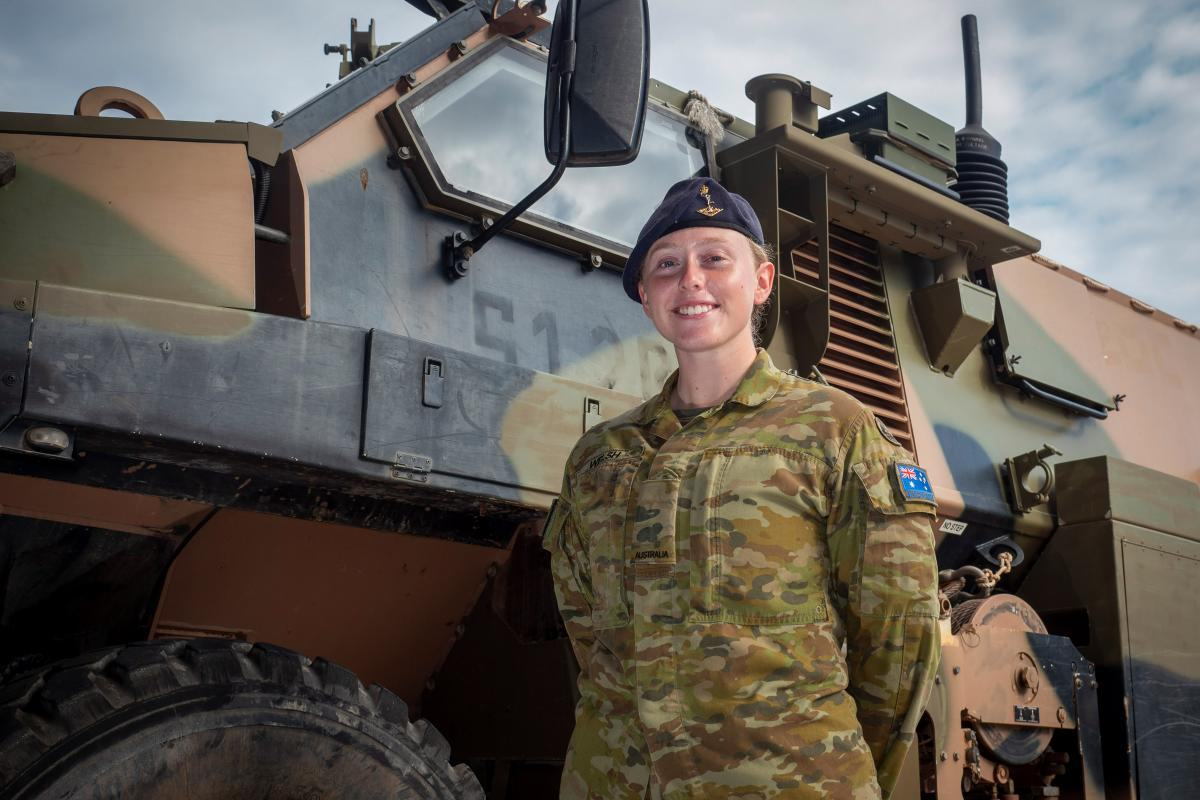 Signaller Catherine Welsh, of the 1st Combat Signal Regiment, stands next to a Bushmaster Protected Mobility Vehicle at Robertson Barracks, Darwin. Photo: Warrant Officer David Millard