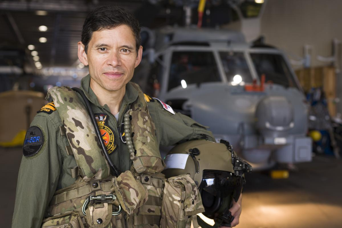 Lieutenant Commander Michael Hardy on board HMAS Adelaide with an MH-60 Romeo he is flying for the Aircraft Maintenance and Flight Trials Unit. Photo: Able Seaman Jarrod Mulvihill