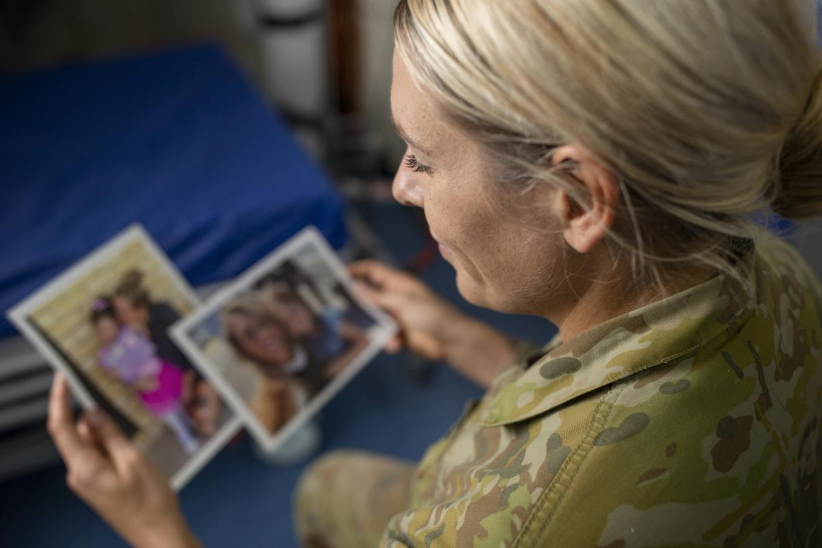 Corporal Sarah Nixon, who is serving in the Middle East, looks at photos of her daughter who she will be thinking of on Mother's Day. Photo: Petty Officer Yuri Ramsey