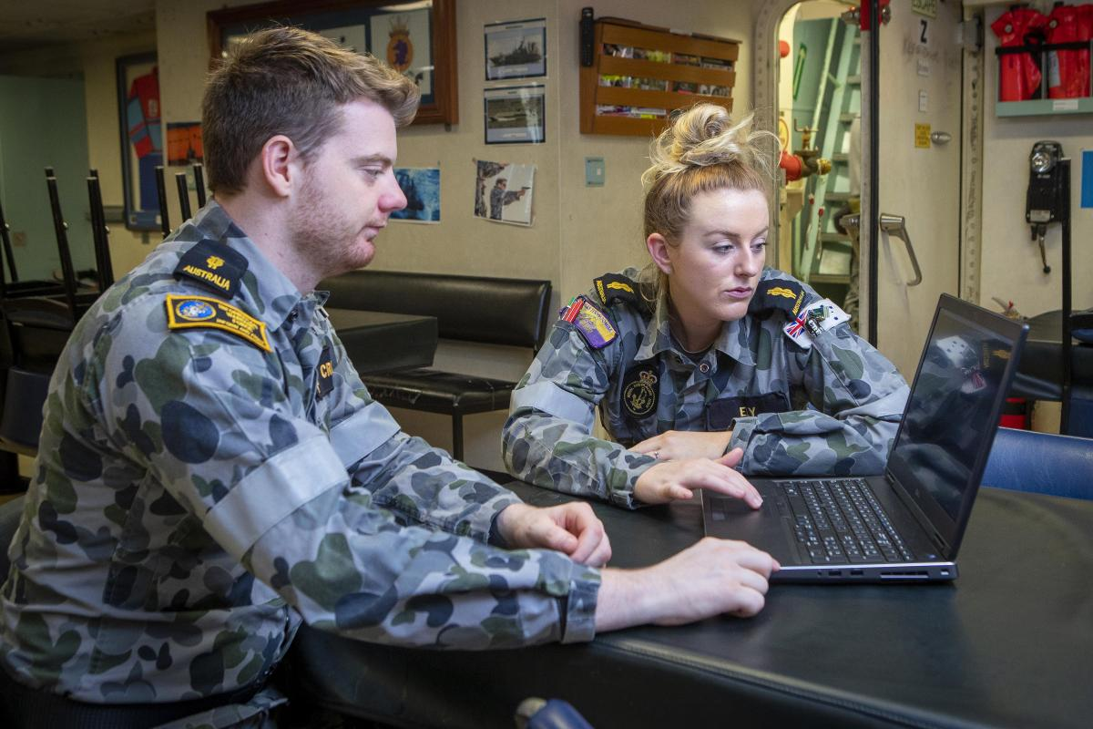 Able Seaman Cryptologic Networks Jackson Cronin explains the results of a test to Able Seaman Communications and Information Systems Brittany Ely on board HMAS Toowoomba. Photo: Leading Seaman Richard Cordell