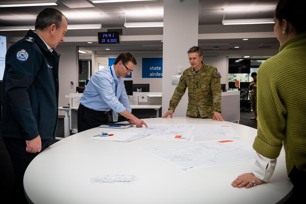 Colonel John Molnar with Emergency Management Victoria and Combined Agency Operations Group representatives at the State Control Centre in Melbourne, Victoria. Photo: Leading Aircraftman John Solomon