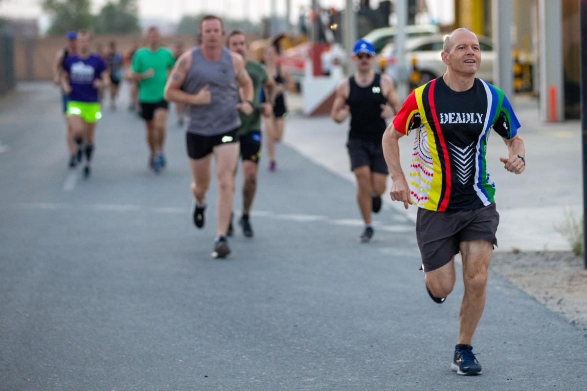 """Deputy Commander Joint Task Force 633 Air Commodore Matthew Hegarty leads the pack during the """"Deadly Fun Run"""" at Australia's main operating base in the Middle East. Photo: Petty Officer Yuri Ramsey"""