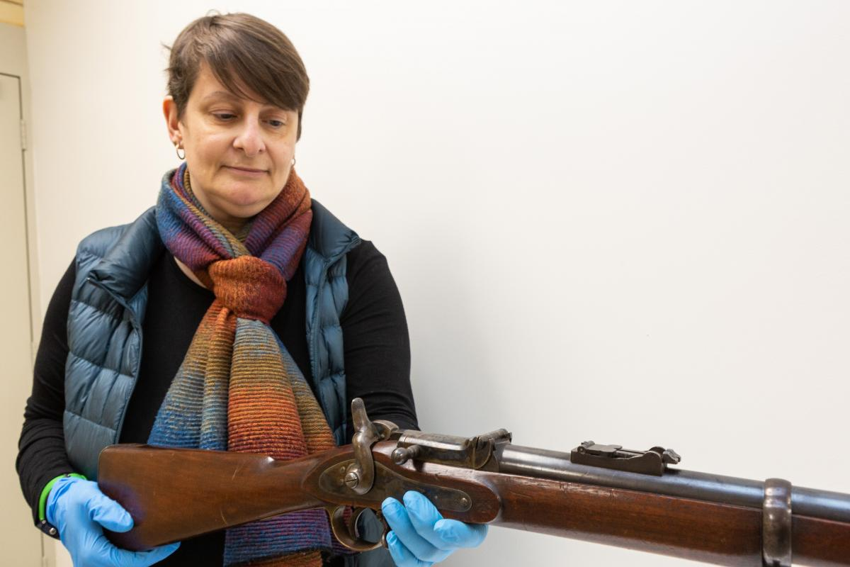 Corinne Ball, Curator History Trust of South Australia, inspects the 1868 Braendlin-Albini rifle. Photo: Leading Aircraftwoman Jacqueline Forrester