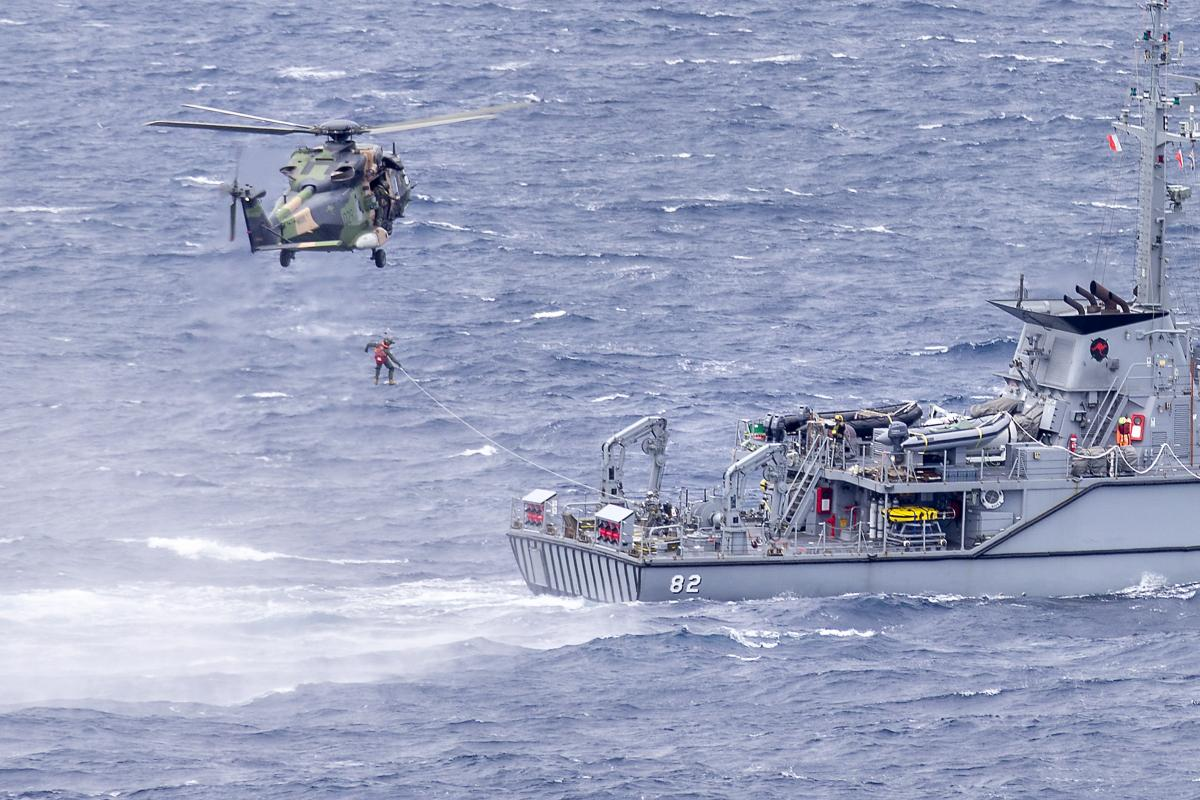 HMAS Choules' embarked MRH-90 Taipan helicopter conducts passenger transfer serials with HMAS Huon during the ship's transit to Vanuatu. Photo: Leading Seaman James McDougall