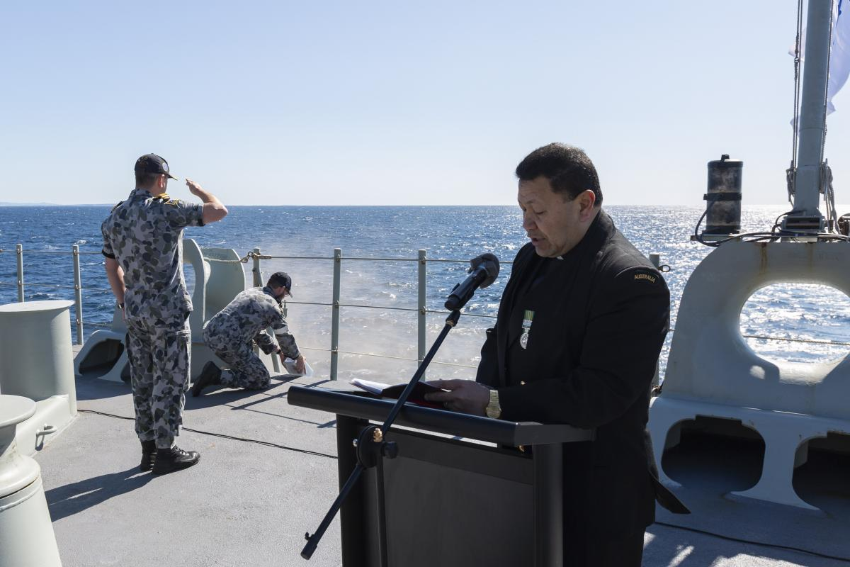 Chaplain Simote Finau and crew of HMAS Adelaide conduct a scattering of ashes memorial service. Photo: Able Seaman Sittichai Sakonpoonpol