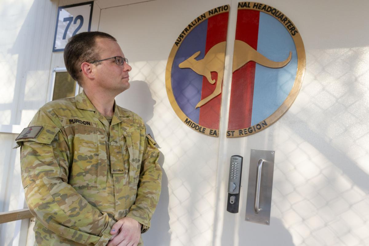 Craftsman Cameron Purdon with his handmade logo on the doors of Headquarters Joint Task Force 633 at Australia's main operating base in the Middle East region. Photo: Major Kris Gardiner