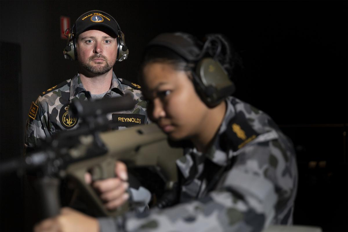 Leading Seaman Bradley Reynolds supervises Able Seaman Armilyn Pontanes during a live-fire serial at the new Weapons Training Simulation System at HMAS Penguin. Photo: Leading Seaman Nadav Harel