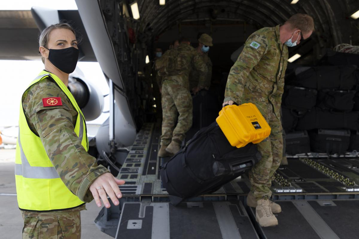 Private Caroline Walker-Campbell helps soldiers disembark a RAAF C-17A Globemaster during operation COVID-19 Assist. Photo: Sergeant Kirk Peacock