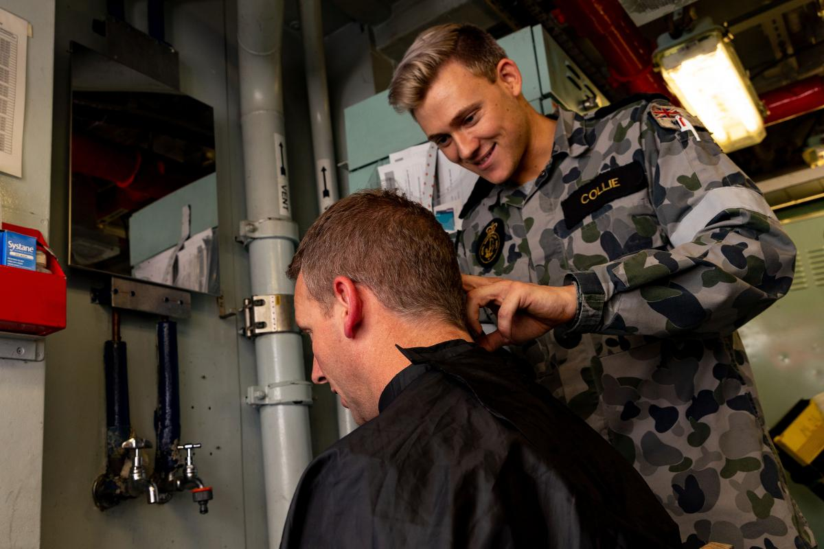Commander Antony Pisani gets his hair cut by Able Seaman Steven Collie while on the Indian Ocean Deployment. Photo: Leading Seaman Shane Cameron