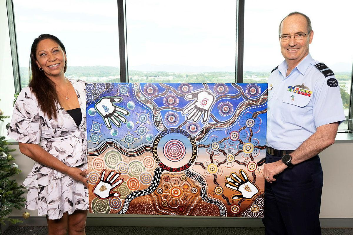 Walbunja artist Katrina Stewart presents her artwork Common Ground to Chief of Air Force Air Marshal Mel Hupfeld at Defence's Russell offices, Canberra. Photo: Petty Officer Lee-Anne Cooper