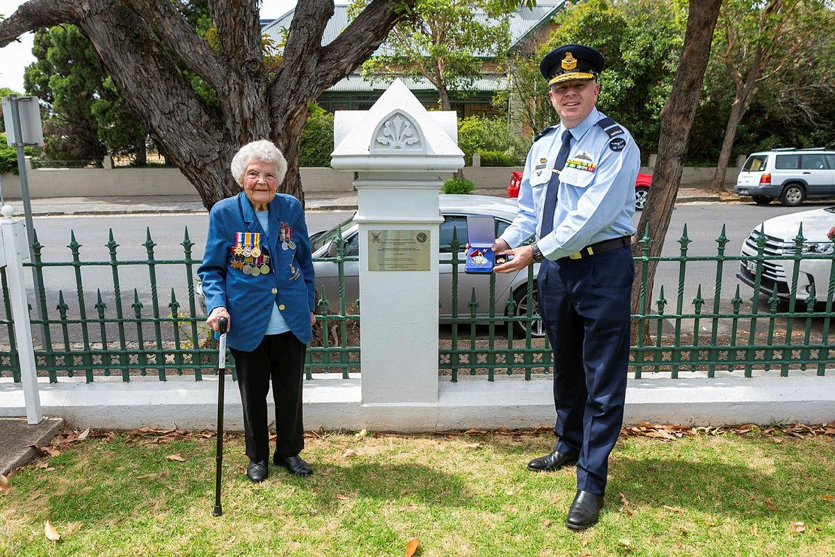 Senior Australian Defence Force Officer - Edinburgh Defence precinct Air Commodore Brendan Rogers presents a US Army Small Ships Section medallion to World War II veteran Thelma Zimmerman. Photo: Leading Aircraftwoman Jacqueline Forrester