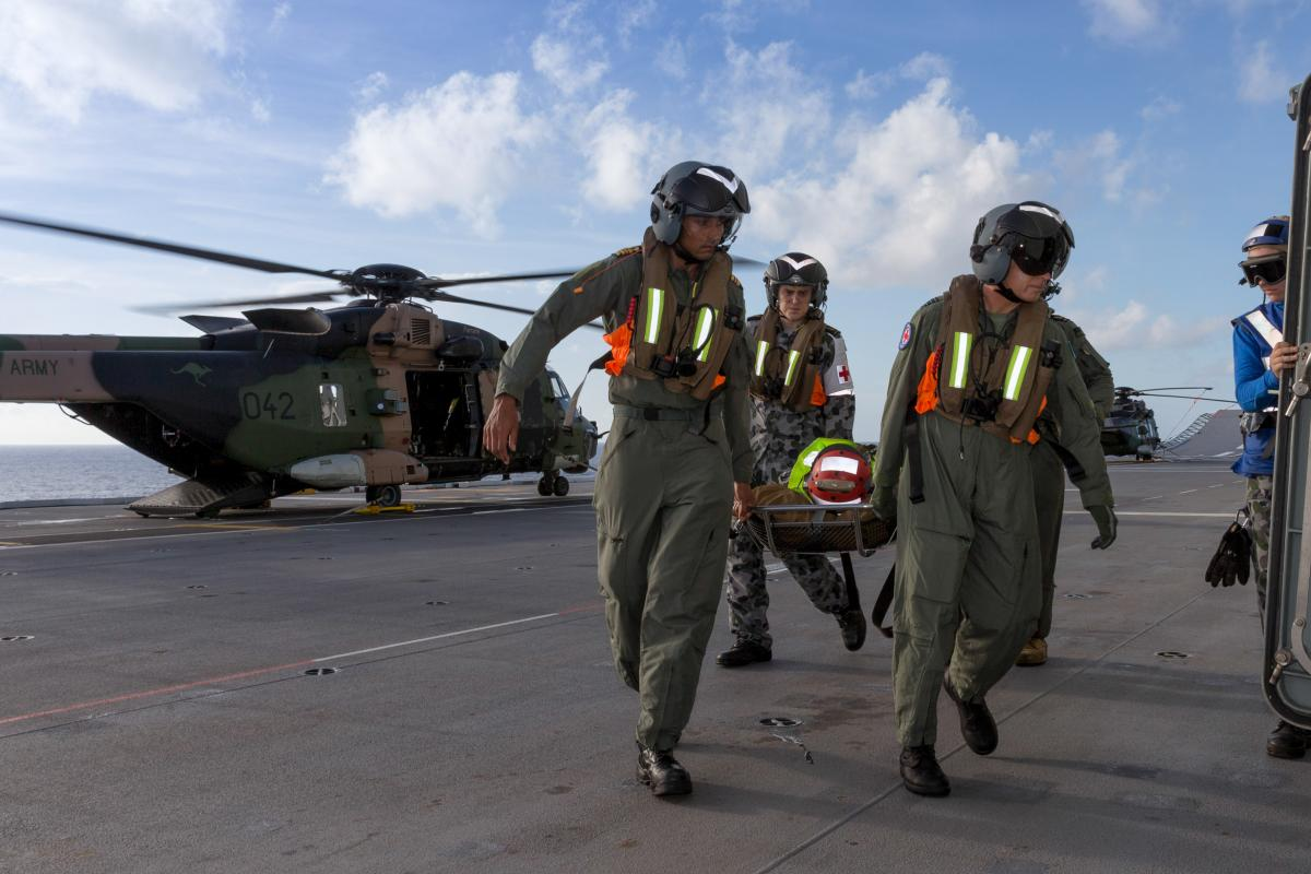 Members of HMAS Canberra's aeromedical evacuation team, from left, Lieutenant Commander Roneel Chandra, Able Seaman Medical Steven Moyle and Wing Commander Shane Brun transfer a patient during a training exercise.