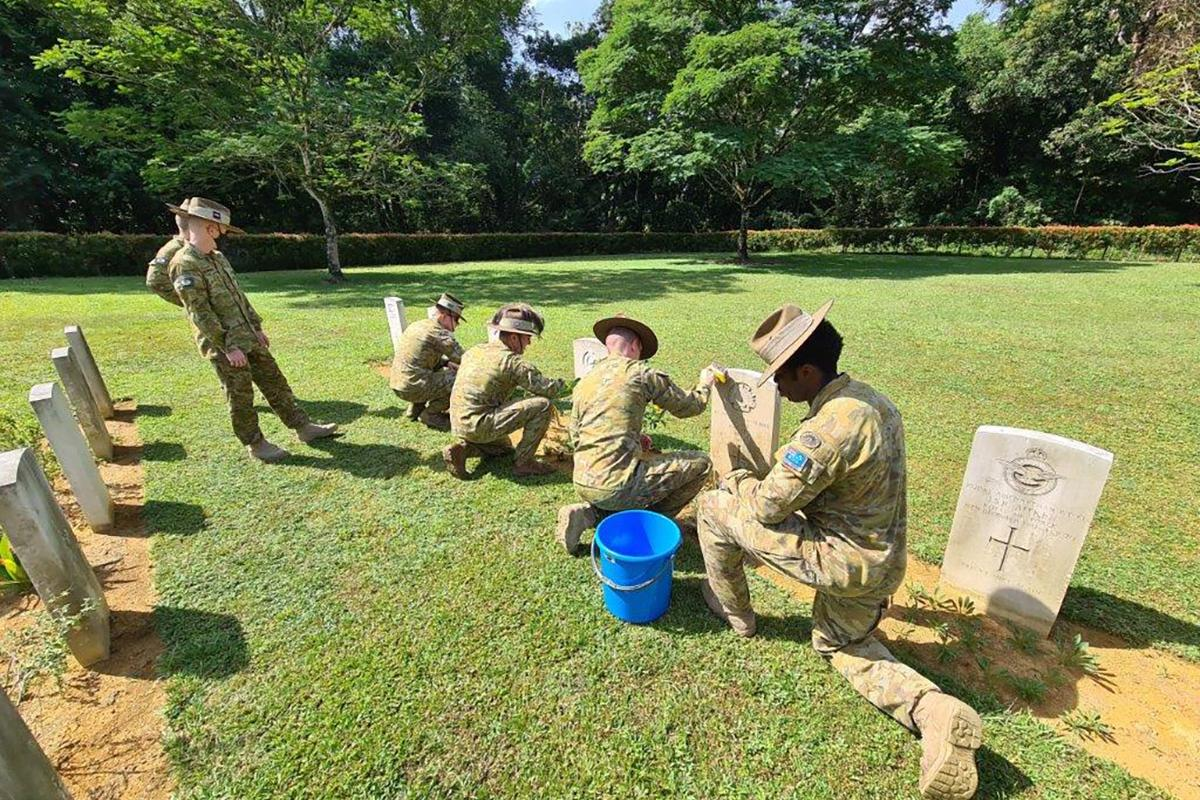 Members of 130th rotation of Rifle Company Butterworth clean the gravestones of fallen Commonwealth service personnel at the Taiping War Cemetery, Malaysia.