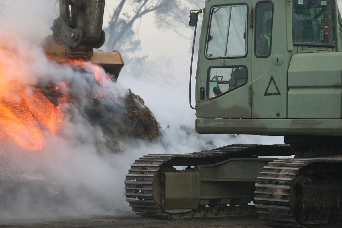 Sapper Mathias Beddie, from the 2nd Combat Engineer Task Group – NSW, pulls down piles of burning mulch. Photo: Major Cameron Jamieson