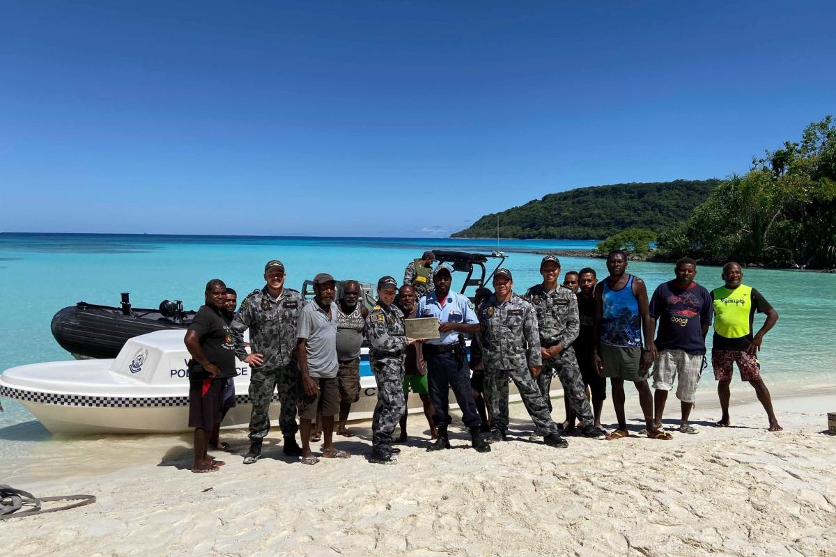 HMAS Melville's Executive Officer Lieutenant Commander Sara Barnett presents Corporal Joe Meto, Vanuatu Police Force, with an HMAS Melville plaque on the safe delivery of the police boat to Loh Island. Photo: Able Seaman Rebecca Churches