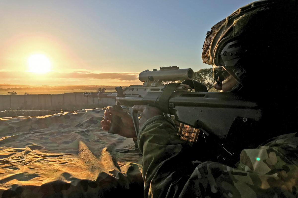 Signaller Imran Lesses stands to as the sun rises over the Murray Bridge Training Area for Exercise Cobra Run. Photo: Signaller Andrew Foote