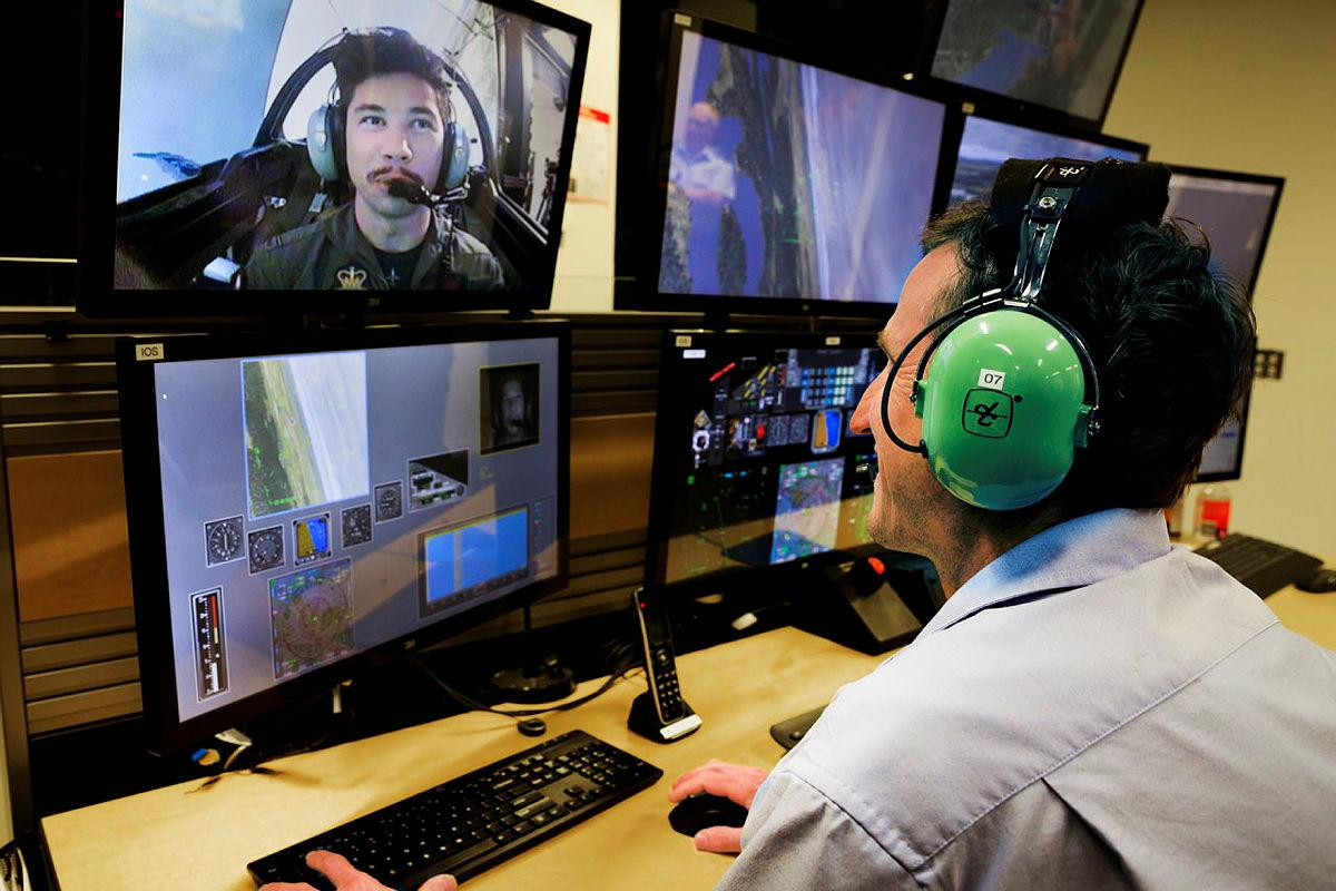 Simulator Pilot Instructor Ben Scorey, of Canadian Aviation Electronics, monitors and instructs Pilot Officer Alec Taylor in the Hawk 127 Simulator during a trial of eye tracking technology. Photo: Corporal Brett Sherriff