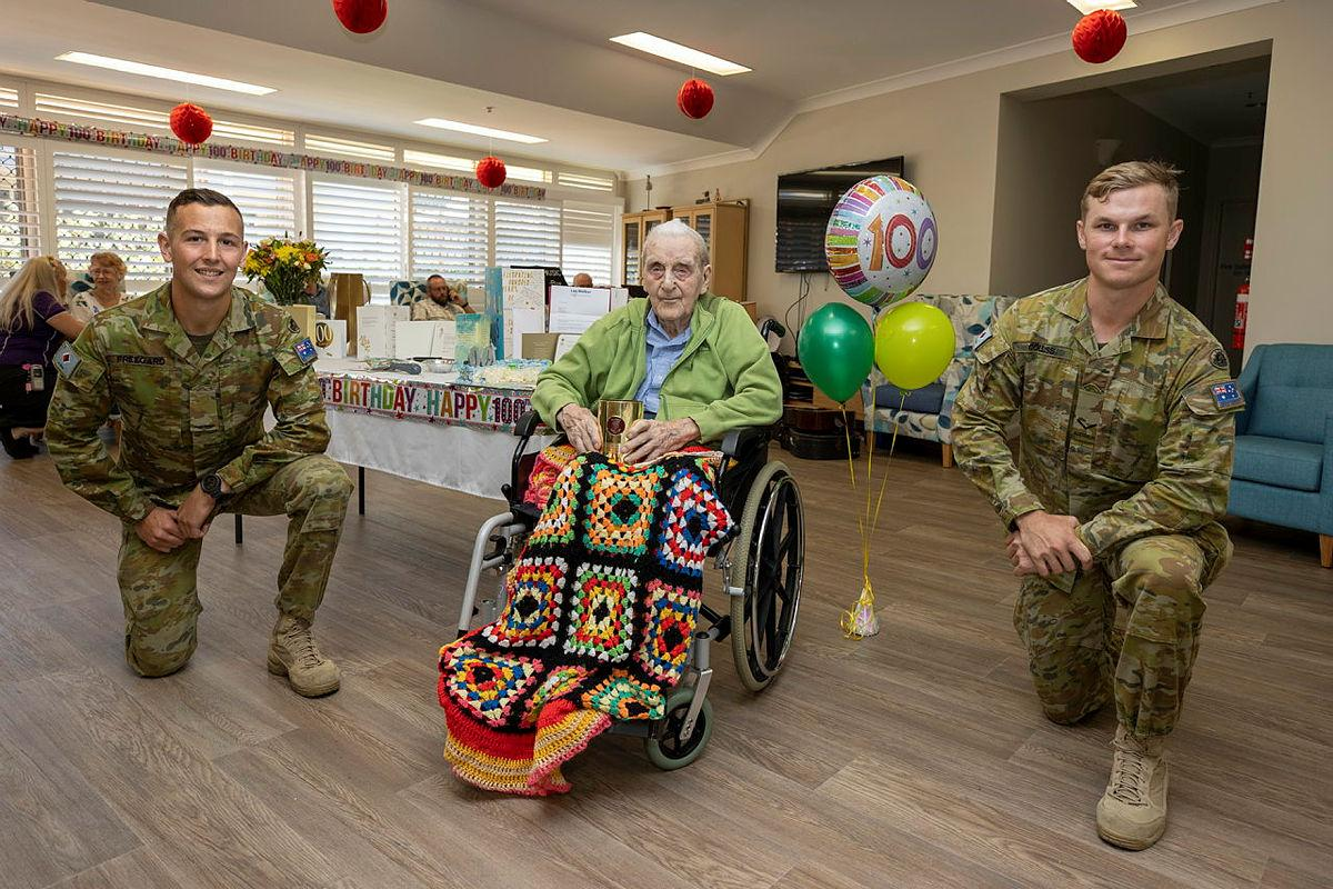 Gunner Matt Freegard, left, and Lance Bombardier Jarrod Colliss, of the 4th Regiment, Royal Australian Artillery with David Shannon on his 100th birthday at Ozcare Townsville. Photo: Corporal Brodie Cross