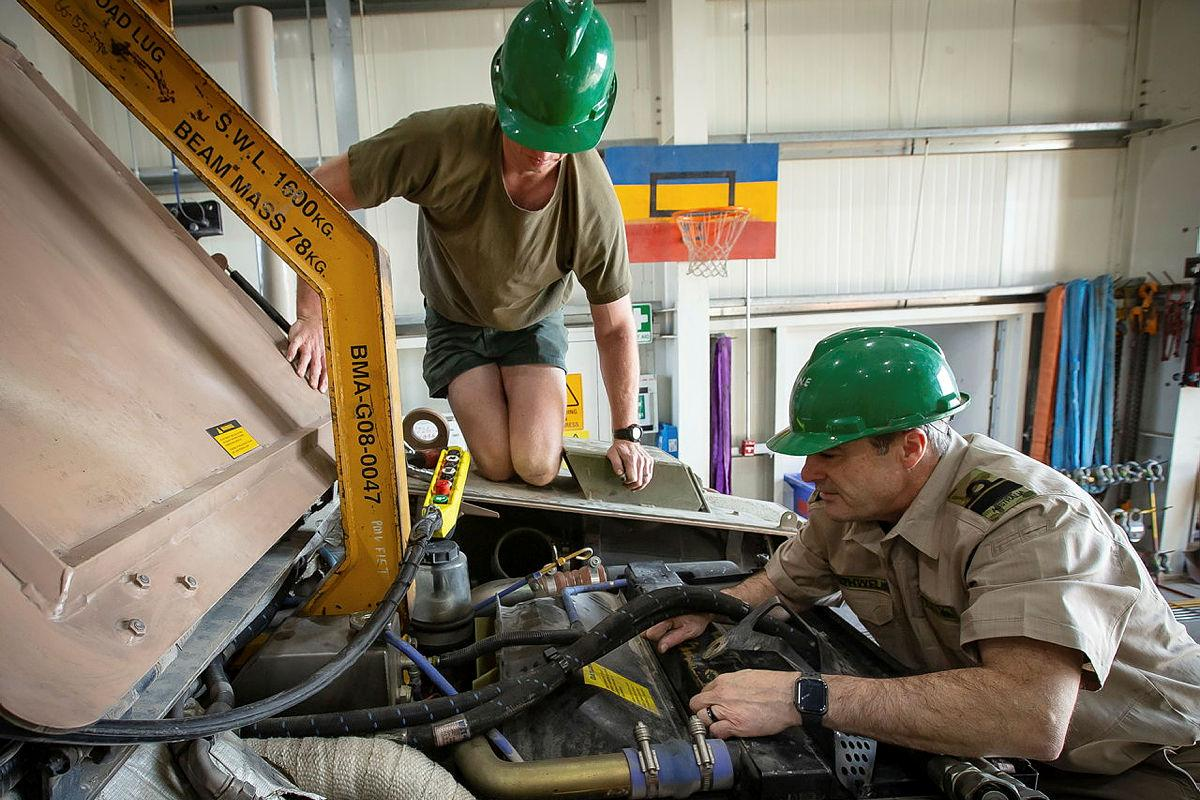 Lance Corporal Cameron Pennell, left, and Rear Admiral Michael Rothwell begin removing the engine from a protected mobility vehicle in the Middle East region. Photo: Sergeant Ben Dempster