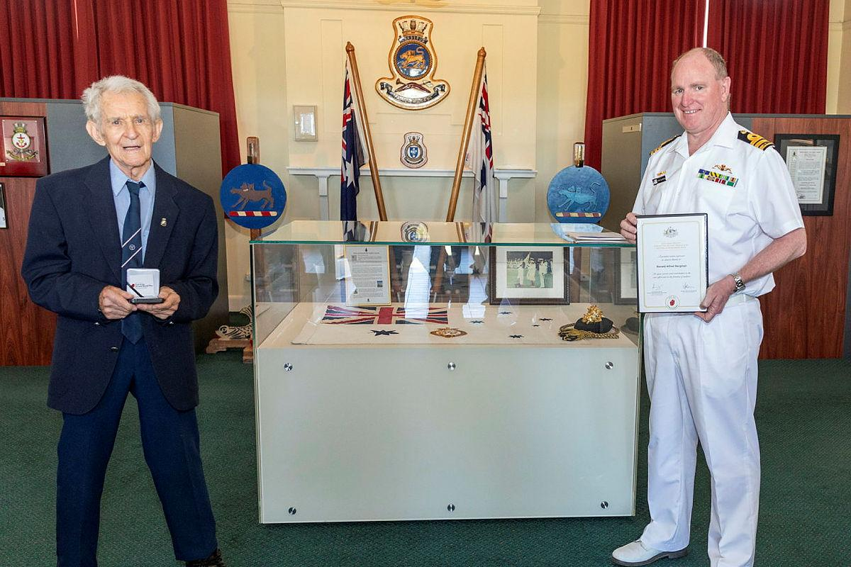 Former Able Seaman Ronald Bergman, 94, is presented a World War II 75th anniversary commemorative medallion by the Executive Officer HMAS Cerberus Commander Martin Holzberger during Mr Bergman's visit to the base. Photo: Leading Seaman James McDougall