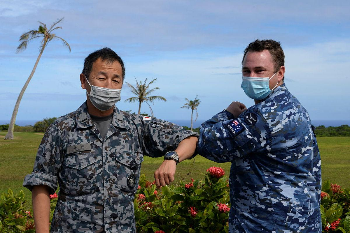 Chaplain Stuart Asquith shares a COVID-safe elbow tap with Warrant Officer Yoshiaki Tanide, of the Japan Air Self-Defense Force at Andersen Air Force Base in Guam. Photo: Technical Sergeant Jerilyn Quintanilla