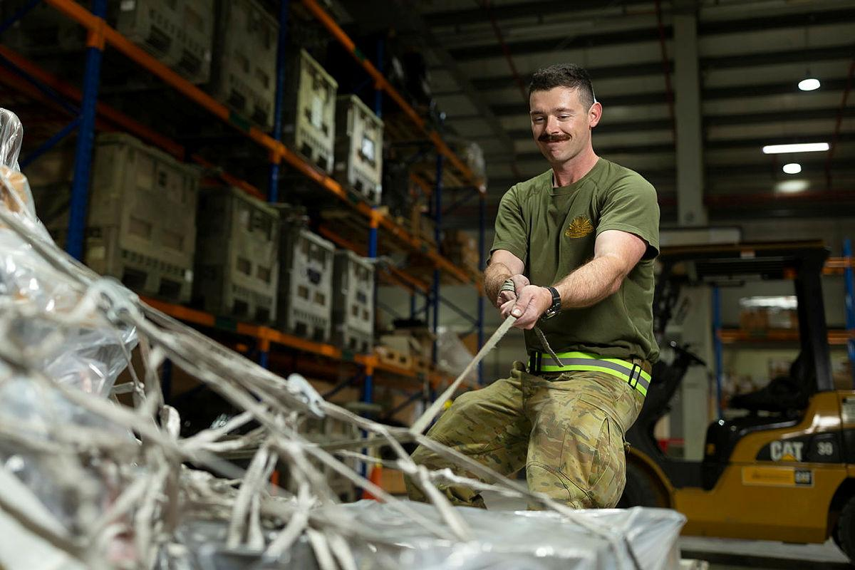 Private Mason Tessier secures cargo pallets in the warehouse of the ADF's main operating base in the Middle East, Camp Baird. Photo: Corporal Tristan Kennedy